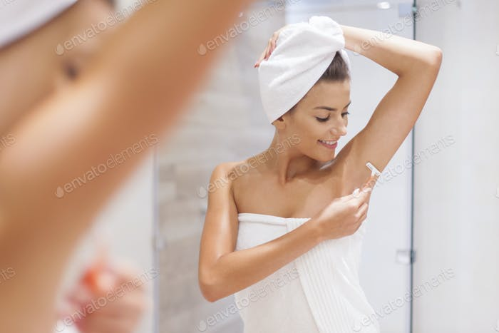 Woman shaving armpit in bathroom