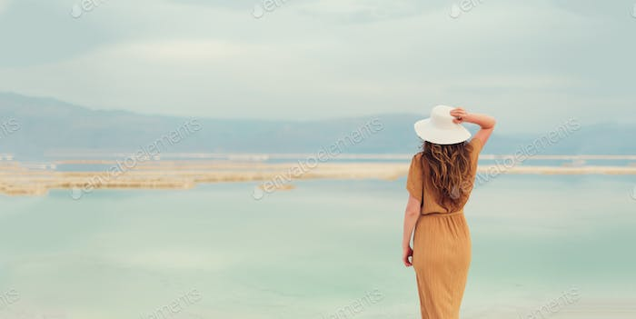 Back view of stylish girl wearing dress on seaside, Dead Sea beach. Travel, summer vacation, holiday