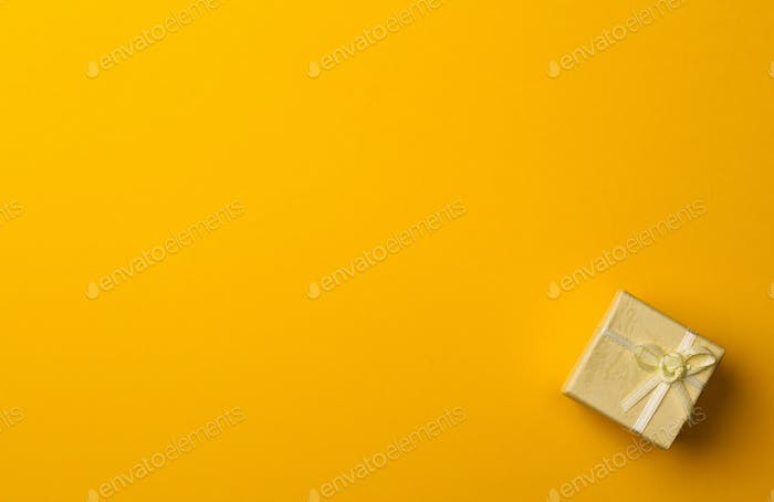 small gift box on yellow paper background