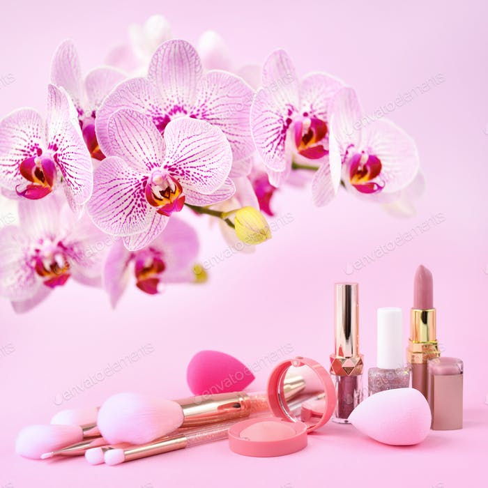 Orchid flowers and decorative cosmetics, sponges  and make-up brushes on a pink background