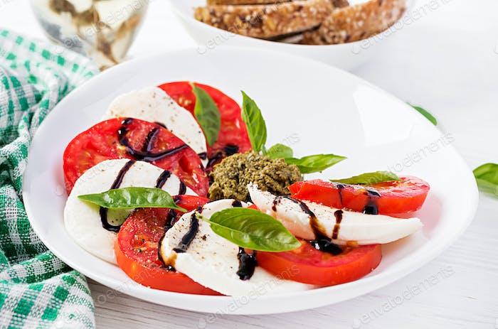 Traditional Italian Caprese Salad with mozzarella, tomato, basil and balsamic vinegar