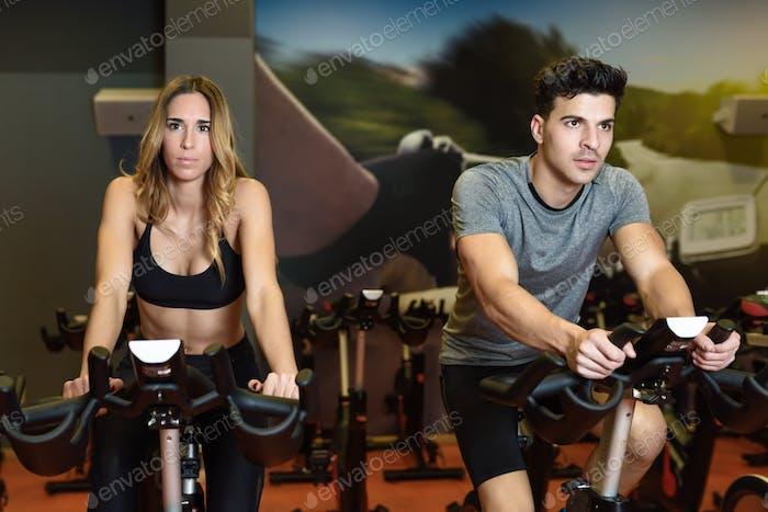 Paar in einer Spinning-Klasse mit Sportbekleidung.