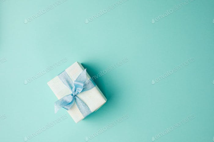 top view of festive decorated christmas gift with ribbon on blue surface