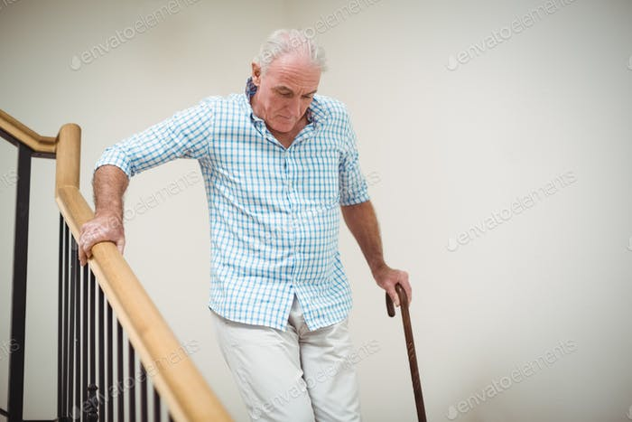 Senior man climbing downstairs with walking stick