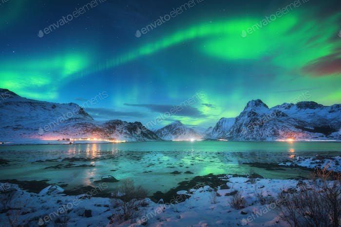 Aurora borealis over the sea coast, snowy mountains and city