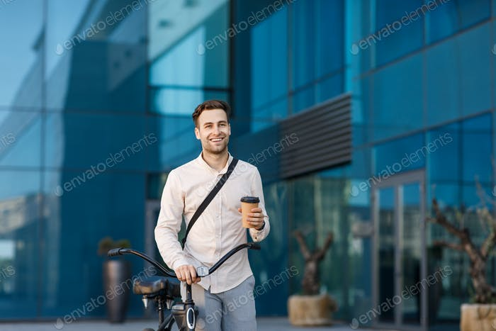 Happy guy with takeaway coffee and bicycle on background of office building goes to work