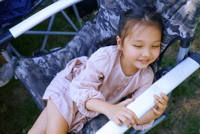 Smiling girl sitting and relaxing on the folding chair