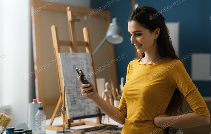Artist working in the studio and chatting with her phone