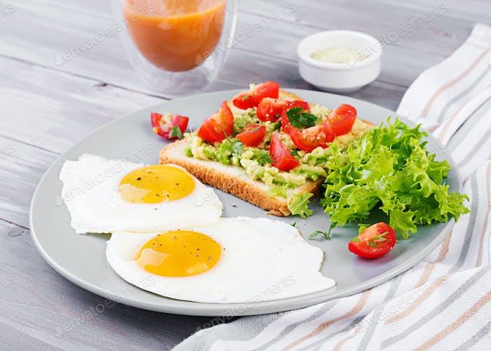 Frühstück. Spiegelei, Gemüsesalat und ein gegrilltes Avocado-Sandwich auf grauem Hintergrund.