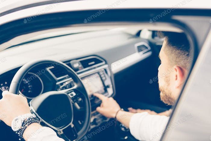 Young man uses automotive navigation system