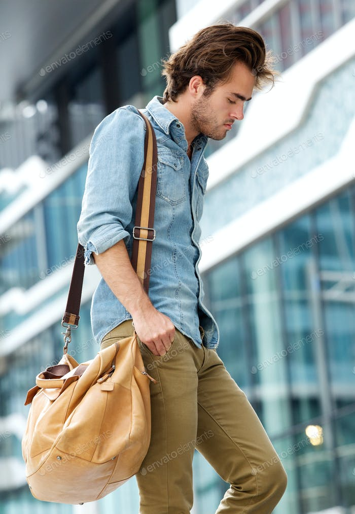Young man walking in the city with travel bag