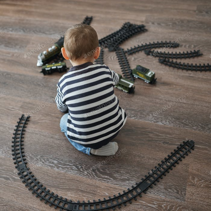 little boy builds toy railroad