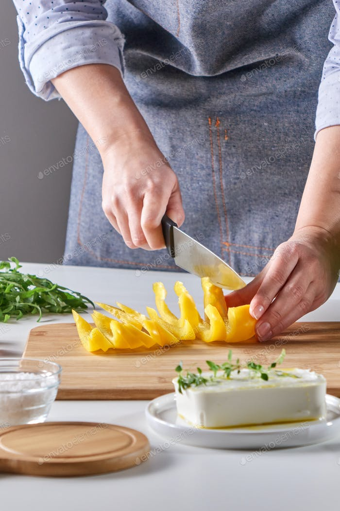 Thumbnail for Woman's hands are cutting organic peppers on a wooden board on a gray table. Cooking salad