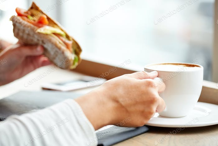 woman drinking coffee and eating sandwich at cafe