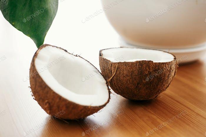 Halbierte Kokosnuss auf Holztisch