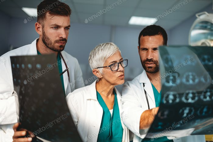 Group of doctors examining an x-ray in hospital to make diagnosis