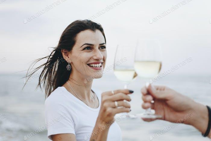Paar genießen ein Glas Wein am Strand