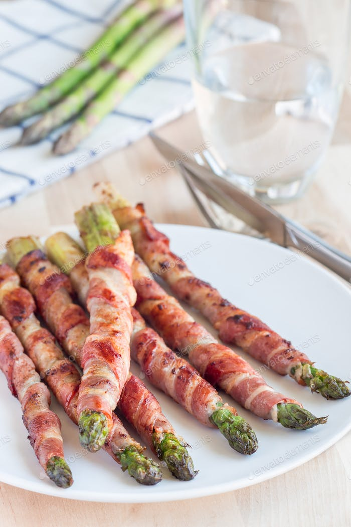 Healthy appetizer, green asparagus wrapped with bacon on a white