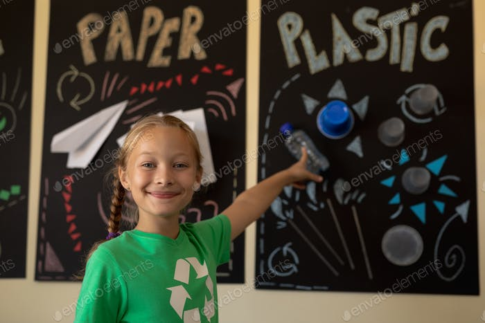 Schoolgirl wearing a green t shirt with a white recycling logo on it and it, pointing to a poster