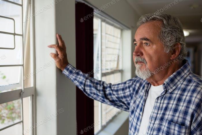 Nachdenklicher Senior Mann durch Fenster im Pflegeheim