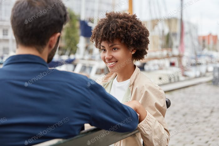 Horizontal shot of romantic couple in love sit on bench against sea port background, have lovely tal