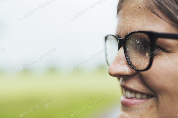 Primer plano de la mujer sonriente en la lluvia