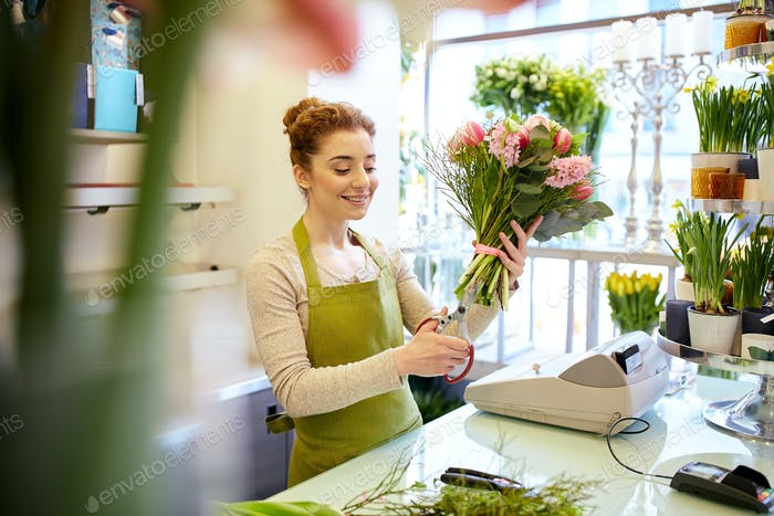 smiling florist woman making bunch at flower shop