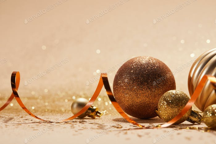 close up of glittering bright christmas balls and wavy ribbon on beige tabletop