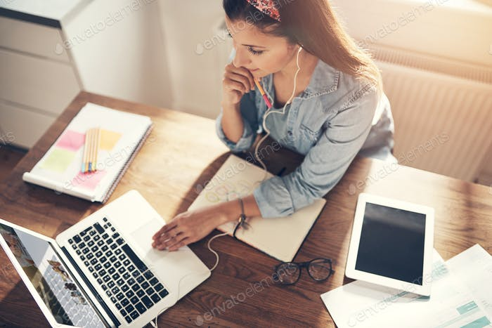 Thoughtful pretty female entrepreneur browsing laptop in office