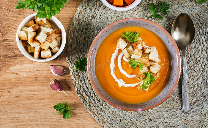 Pumpkin soup in a bowl served with parsley and croutons. Vegan soup.