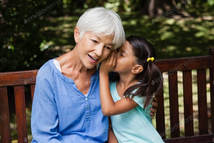 Girl whispering in ears of grandmother while sitting on wooden bench