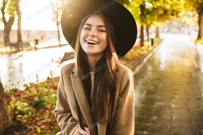 Portrait of joyful woman wearing coat and hat walking in autumn park