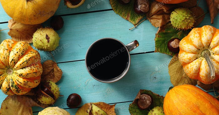 Cup of coffee surrounded by pumpkins