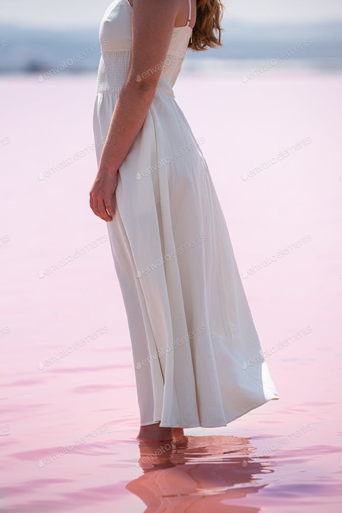 Side view of crop unrecognizable woman wearing white dress standing on an amazing pink lake