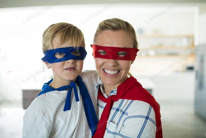 Portrait of mother and son pretending to be superhero in living room