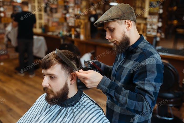 Friseur hält Kamm und schneidet die Haare des Kunden