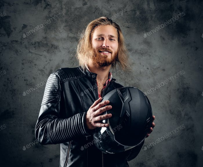 A man in leather jacket holds motorcycle helmet.