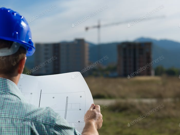 architect reading technical drawing of construction