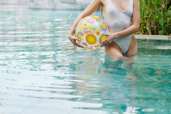 Woman standing in pool with inflatable ball