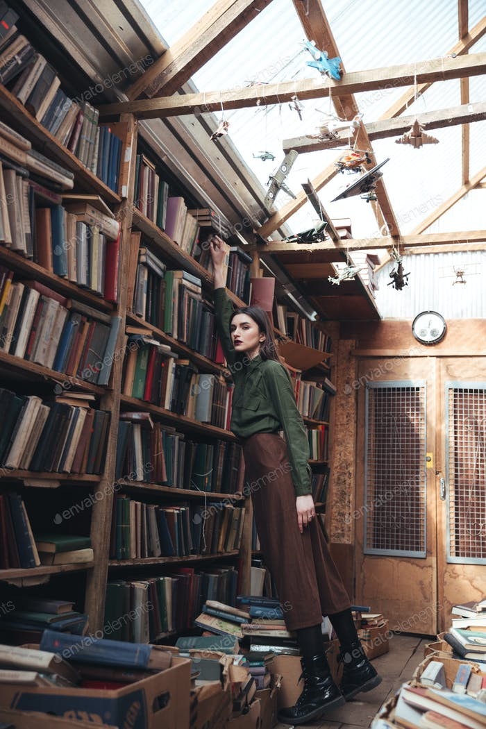 Full-length shot of young woman in library