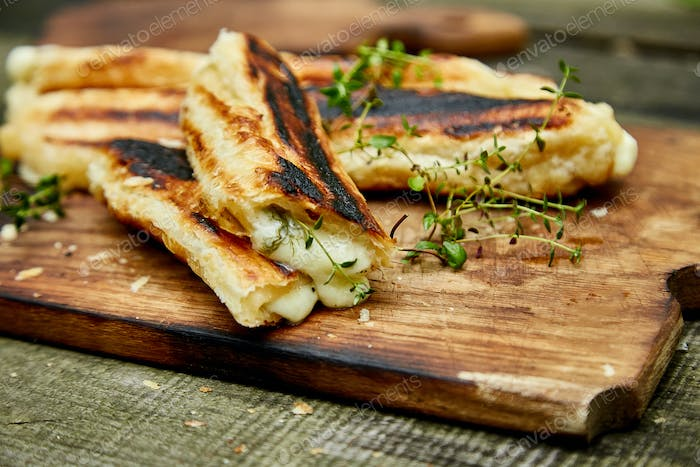 Grilled cheese puff pastry on the wooden cutting board.