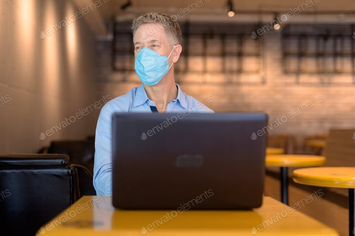 Mature businessman with mask thinking while using laptop at the coffee shop