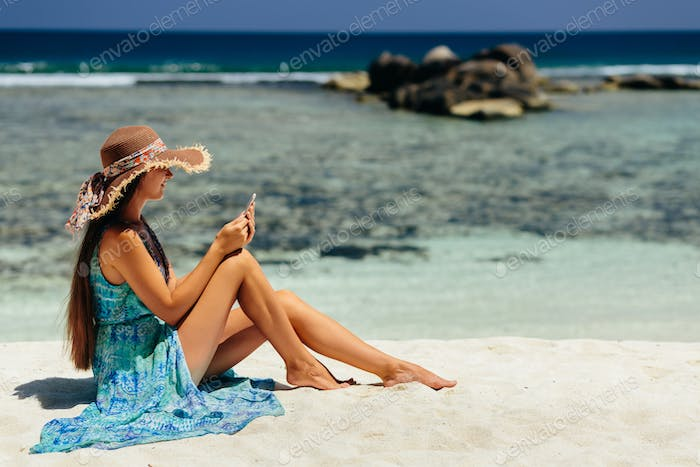 luxury woman using smartphone on beach