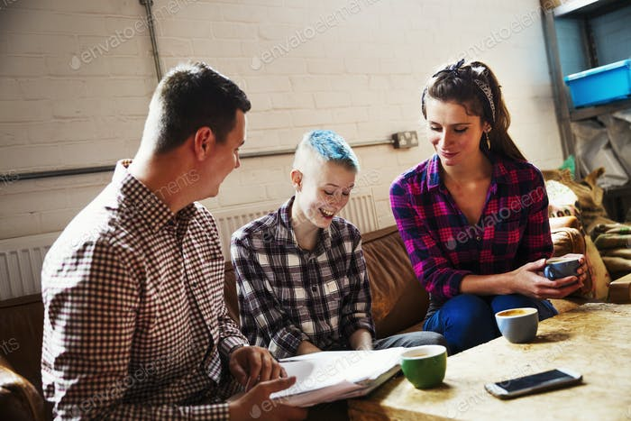 Spezialist Coffee-Shop. Drei Personen, zwei Erwachsene und ein junger Mensch, der auf einem Sofa sitzt.