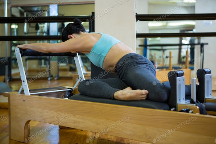 Woman performing stretching exercise on reformer
