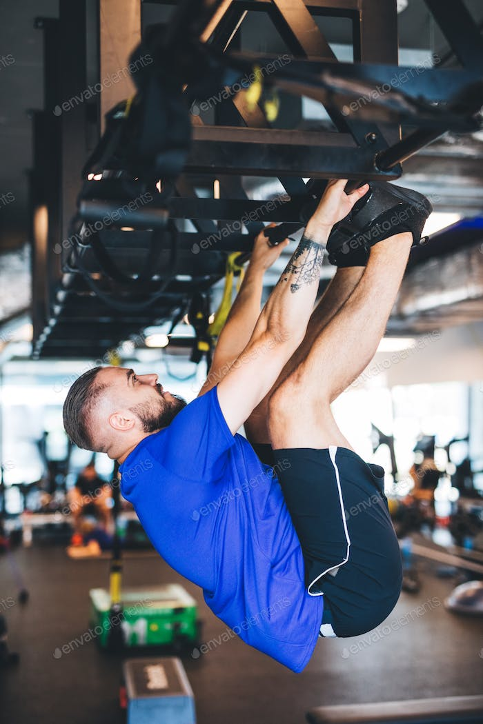 Man pulling his body up on the rig at the gym.
