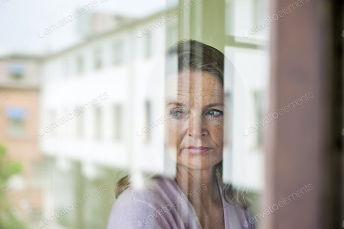 Mature teacher looking away with reflection of school building on glass window