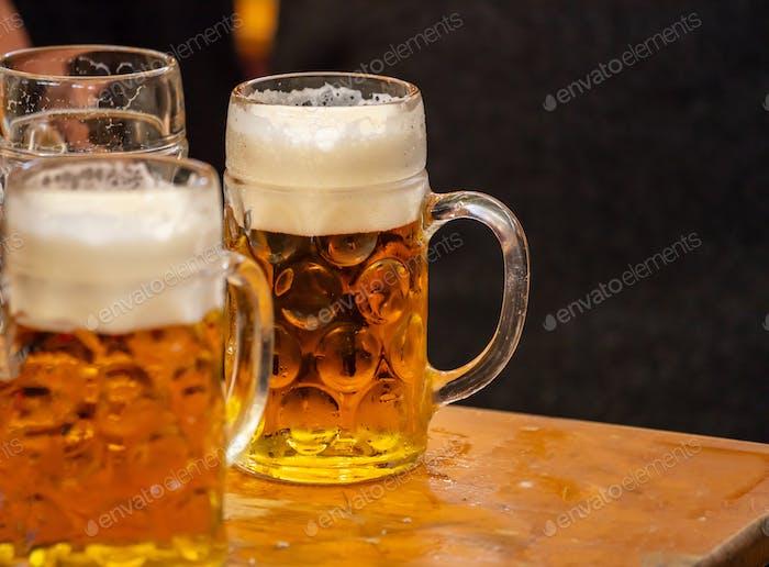 Mugs of beer on a wooden table, closeup view. Oktoberfest, Munich, Bavaria