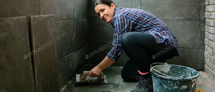 Female mason laying a new tile floor