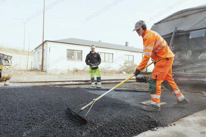 Full length of manual worker with rake spreading asphalt on street